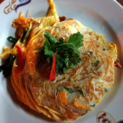Pad thai served inside a thin omelette
