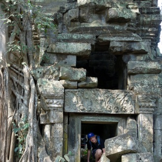 Jesse climbing through some of the ruins at Ta Prohm