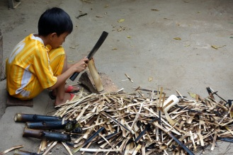 Boy working slicing charred bamboo off of sticky rice.