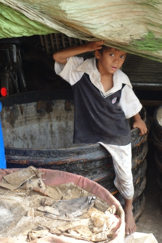 Little boy peaking out at fish paste factory/market