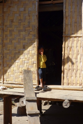 Peering out of M'nong longhouse