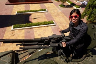 Andrea on a tank a war memorial near Kon Tum