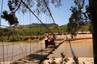 Very wobbly suspension bridge. The locals carry bags of tapioca across.
