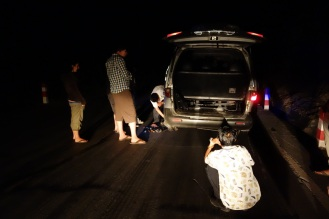 Flat tire repair job (i.e. bunch of men standing around pretending that they know what they are doing)