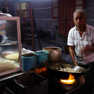Char kway teow stall. Cooked over charcoal, fanning with one hand to get the heat up.