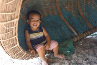 Our favourite little boy hiding under a fishing boat