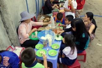 Kids eating their breakfast in the morning market