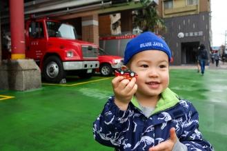 Daniel showing us his toy firetruck in front of the fire station!